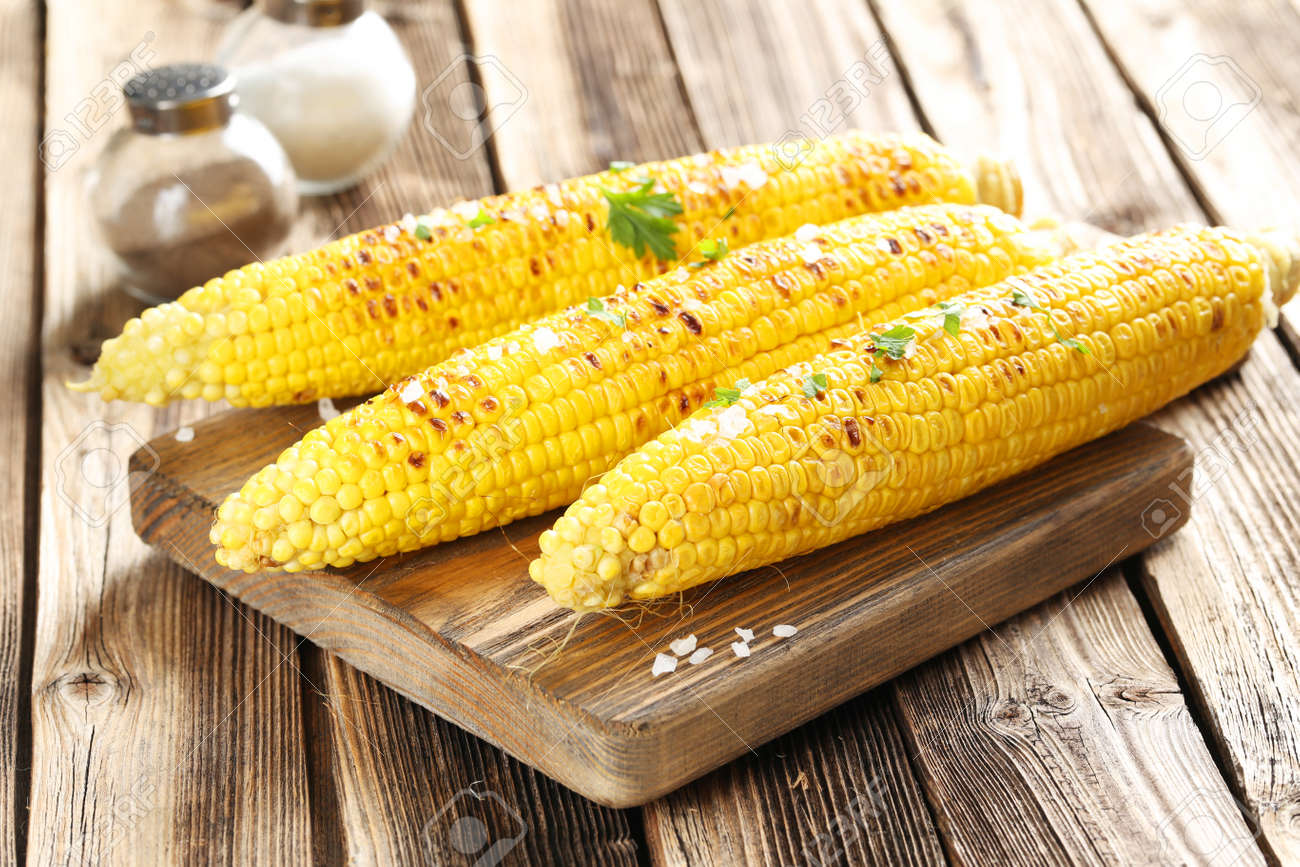 Fresh tasty grilled corn with butter on brown table and cutting board - 44027276