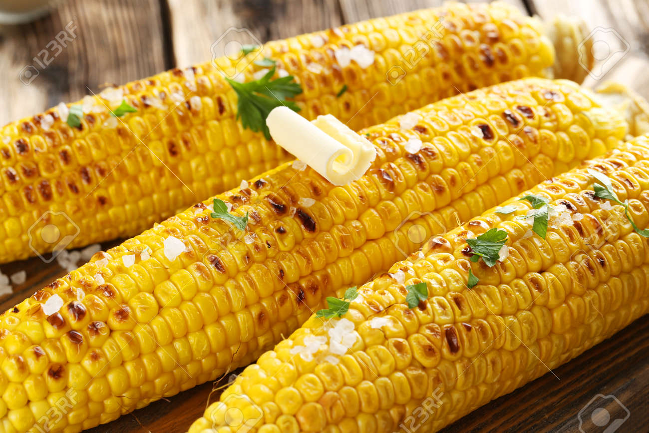 Fresh tasty grilled corn with butter on brown table - 44384209