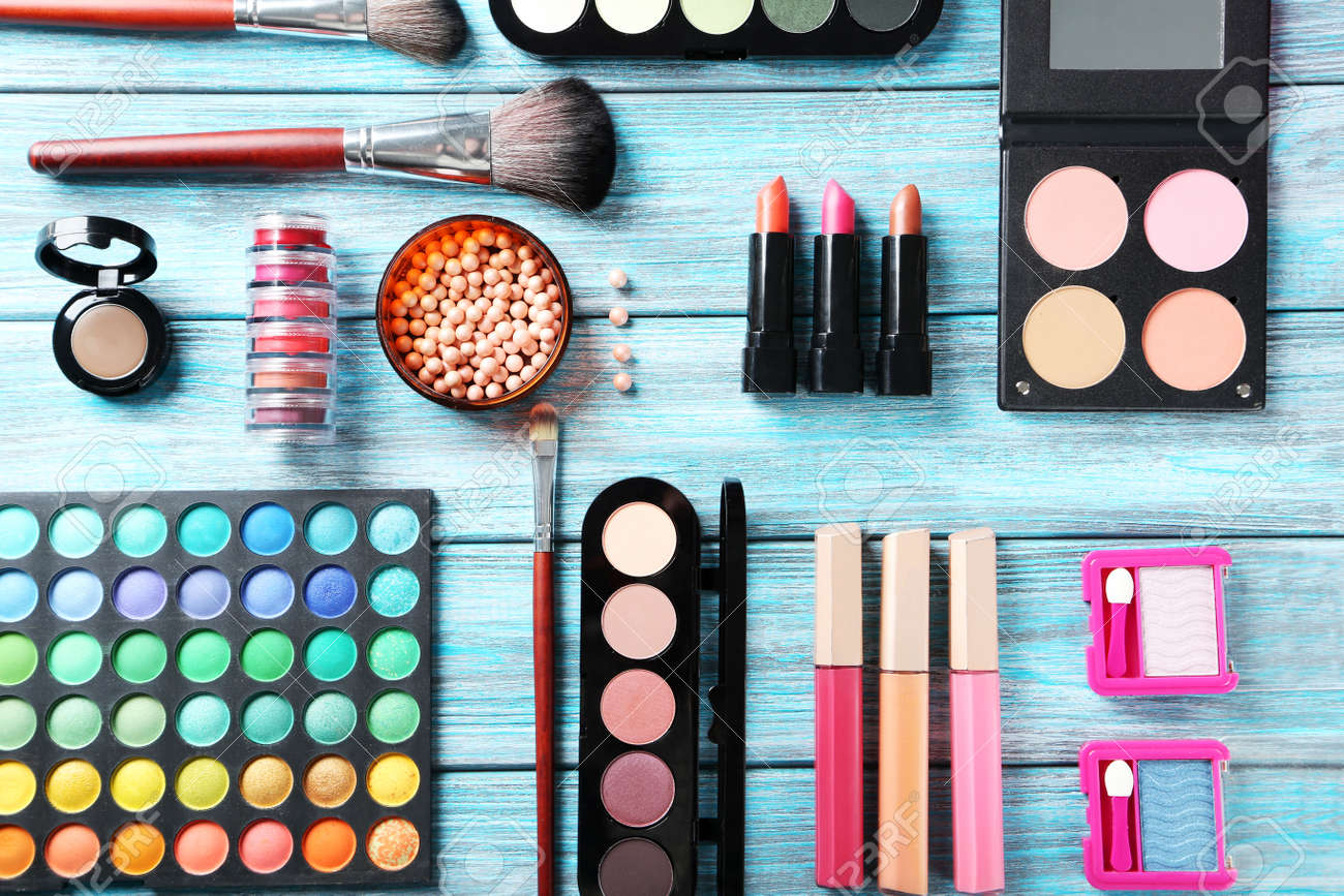 Makeup brush and cosmetics on blue wooden table - 45985968