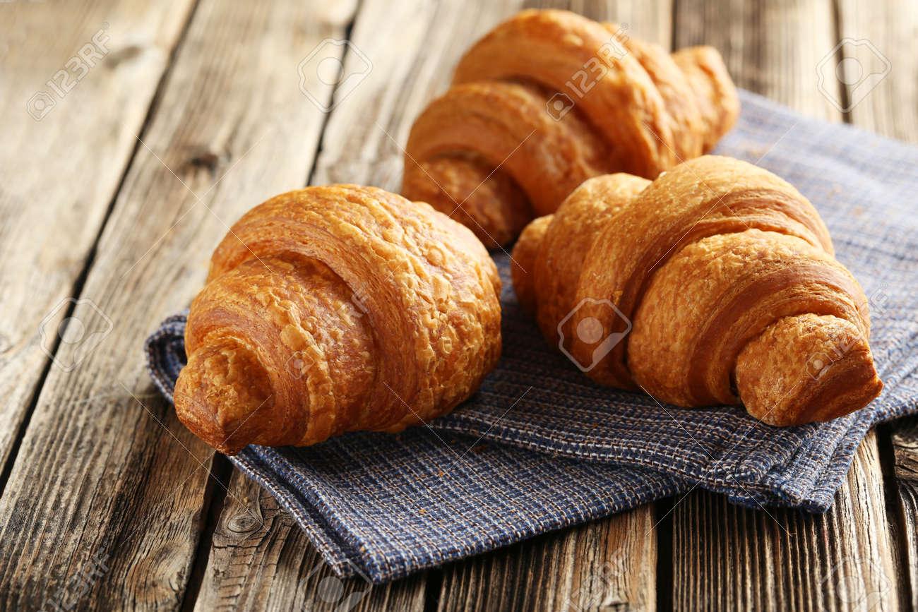 Tasty croissants on brown wooden background - 47628956