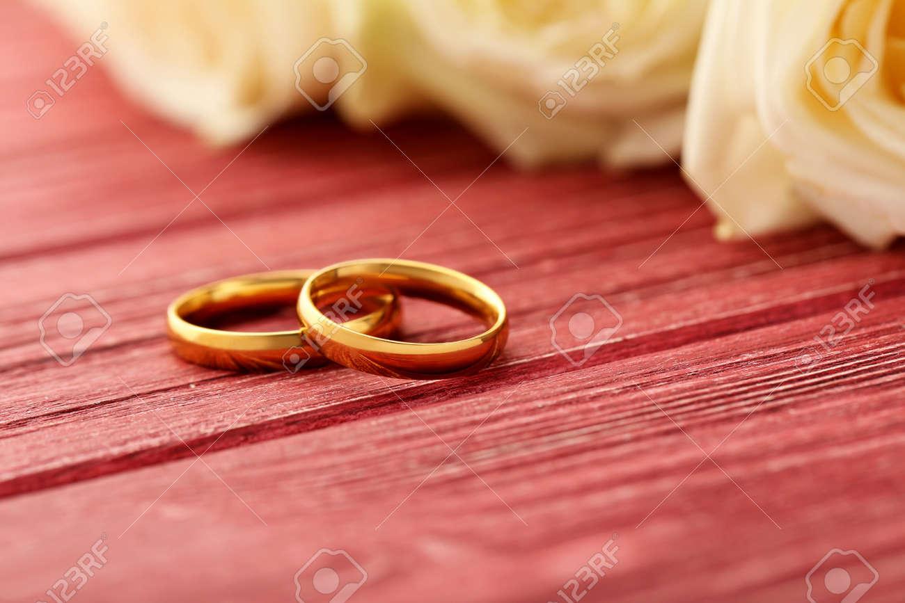 Goldene Hochzeit Ringe Auf Einem Roten Holztisch Lizenzfreie Fotos