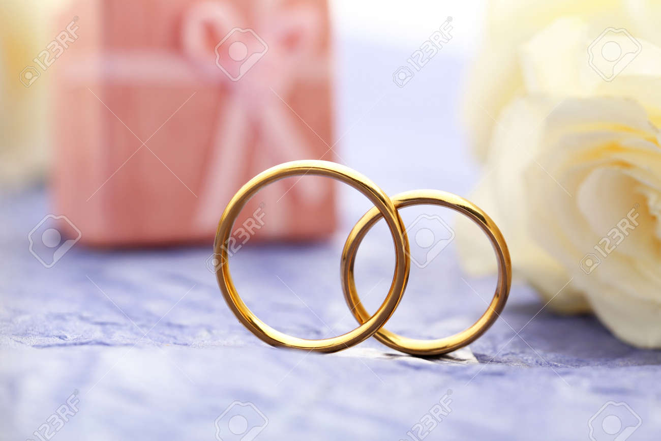 Golden Wedding Rings On A Purple Paper Background Stock Photo ...