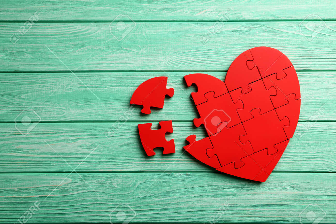Red puzzle heart on mint wooden background - 49913494