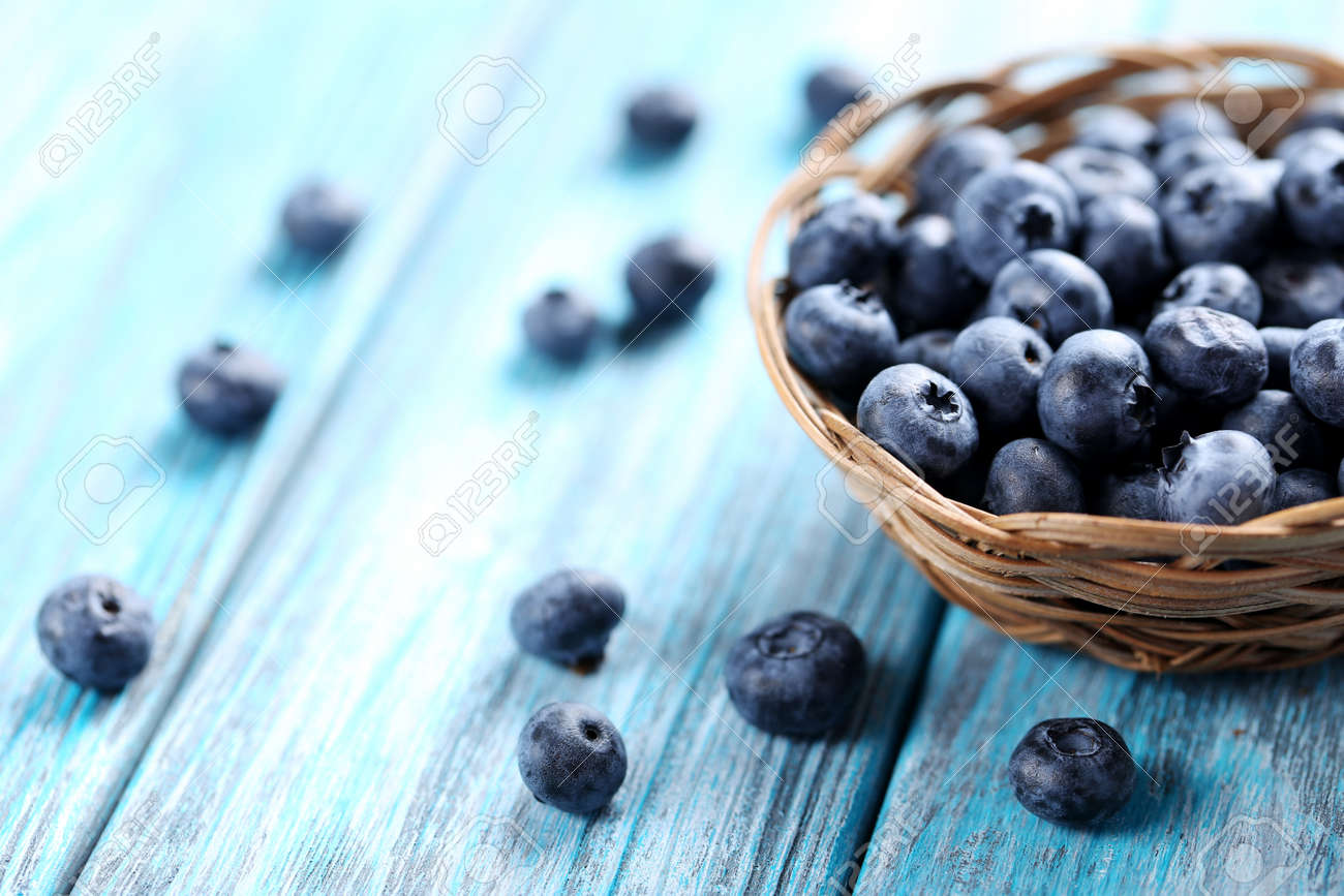 Tasty blueberries in basket on a blue wooden table - 50092681
