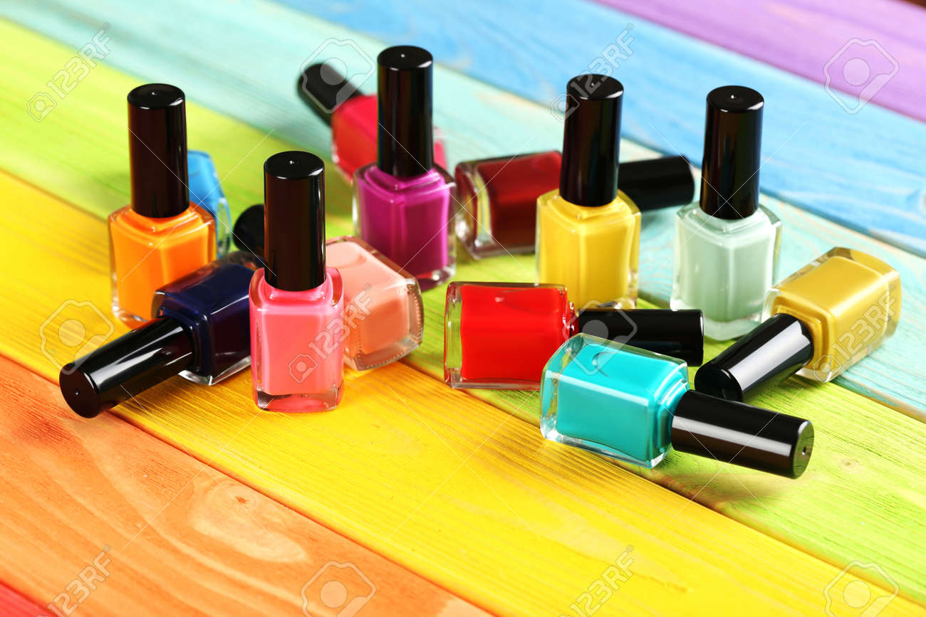 Bottles of nail polish on a colorful wooden table - 50299655