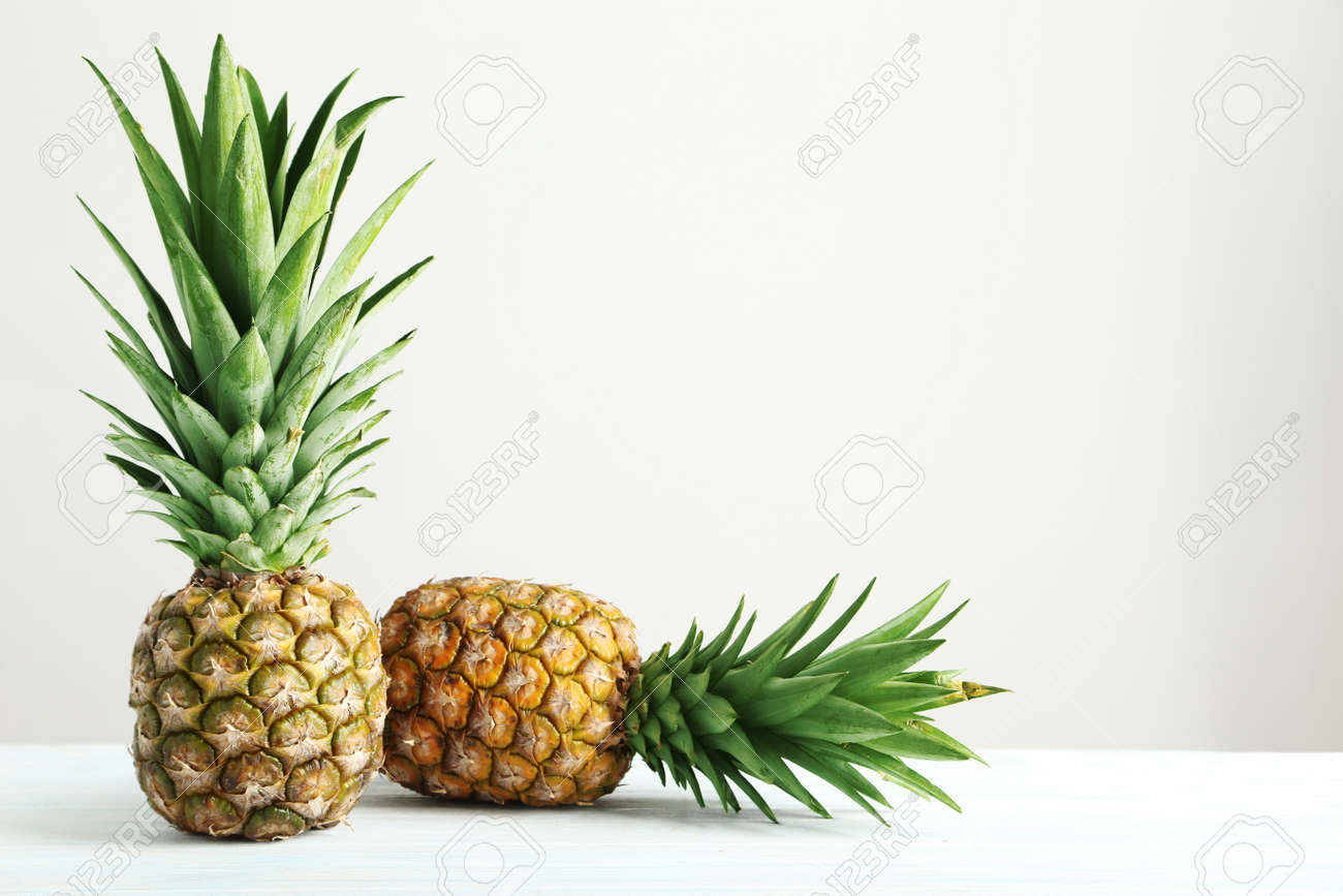 Ripe pineapples on a white wooden table - 51101692