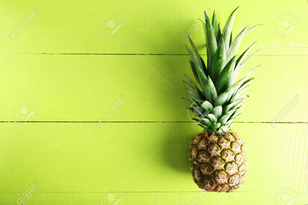Ripe pineapple on a green wooden background - 51101852