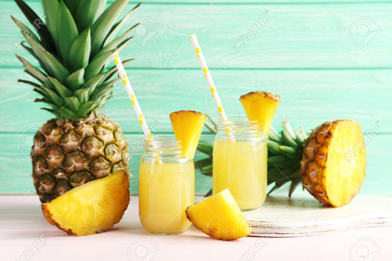 Bottles of pineapple juice on a pink wooden table - 51102030
