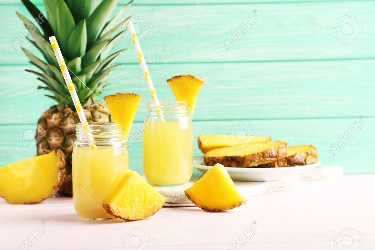 Bottles of pineapple juice on a pink wooden table - 51102031