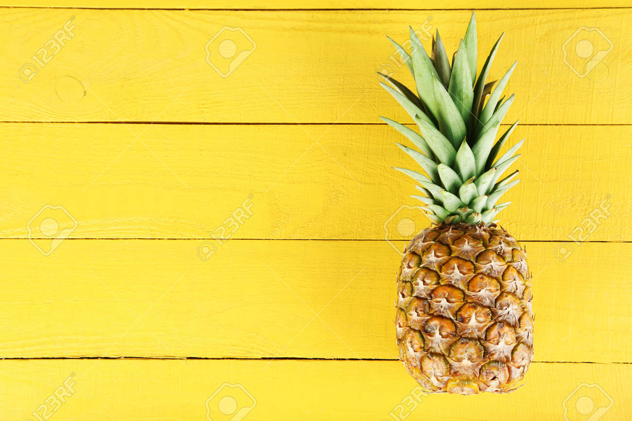 Ripe pineapple on a yellow wooden background - 51102174