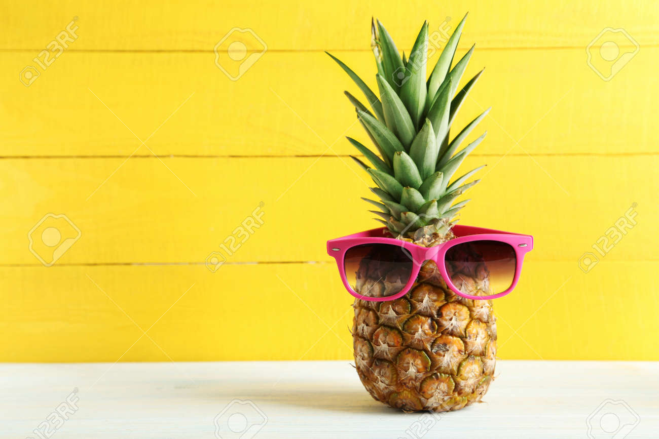 Ripe pineapple with sunglasses on a white wooden table - 51480514