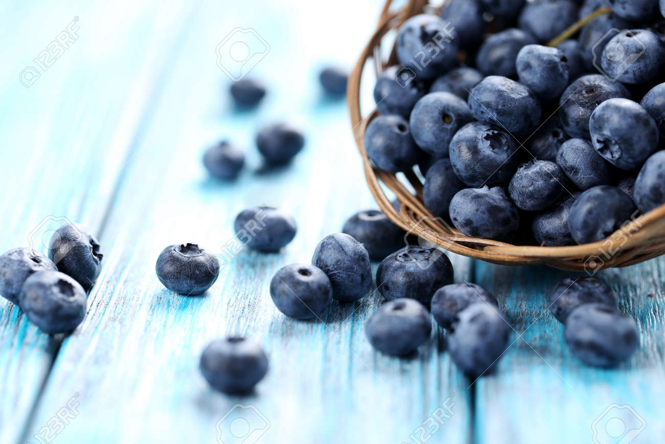 Tasty blueberries in basket on a blue wooden table - 51612251