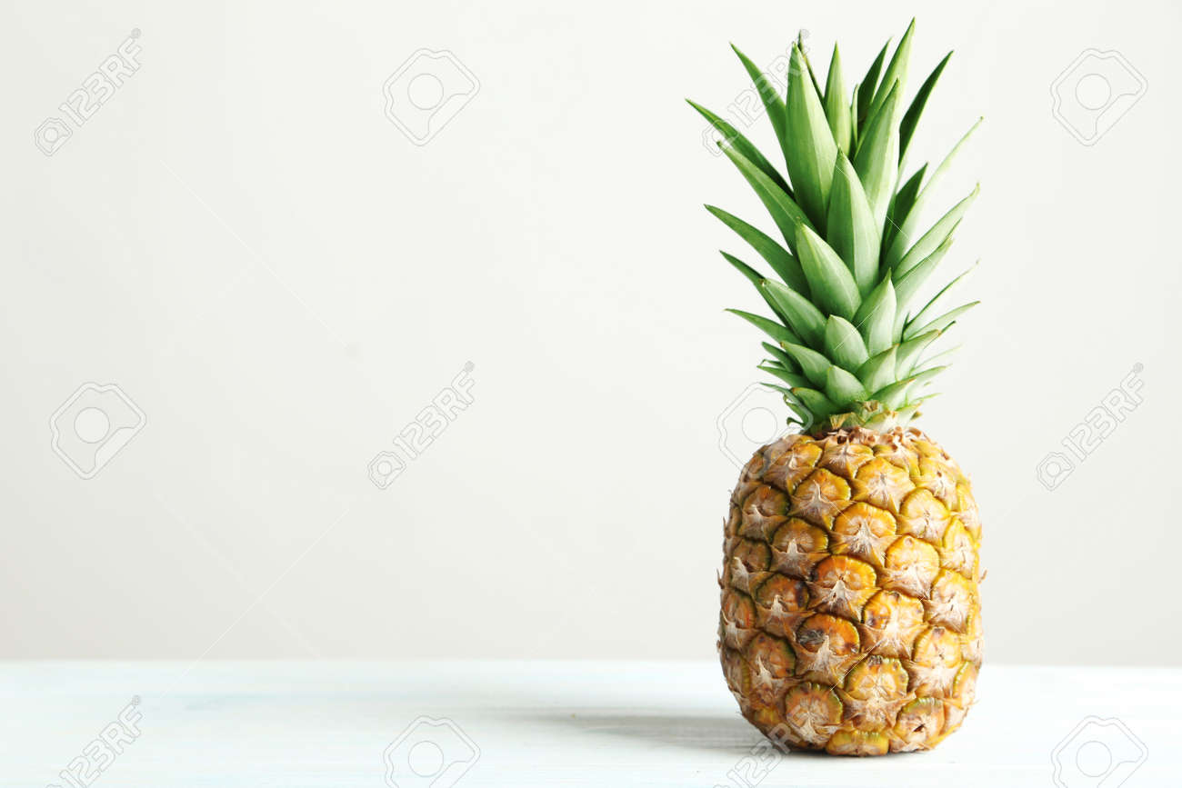 Ripe pineapple on a white wooden table - 52059024