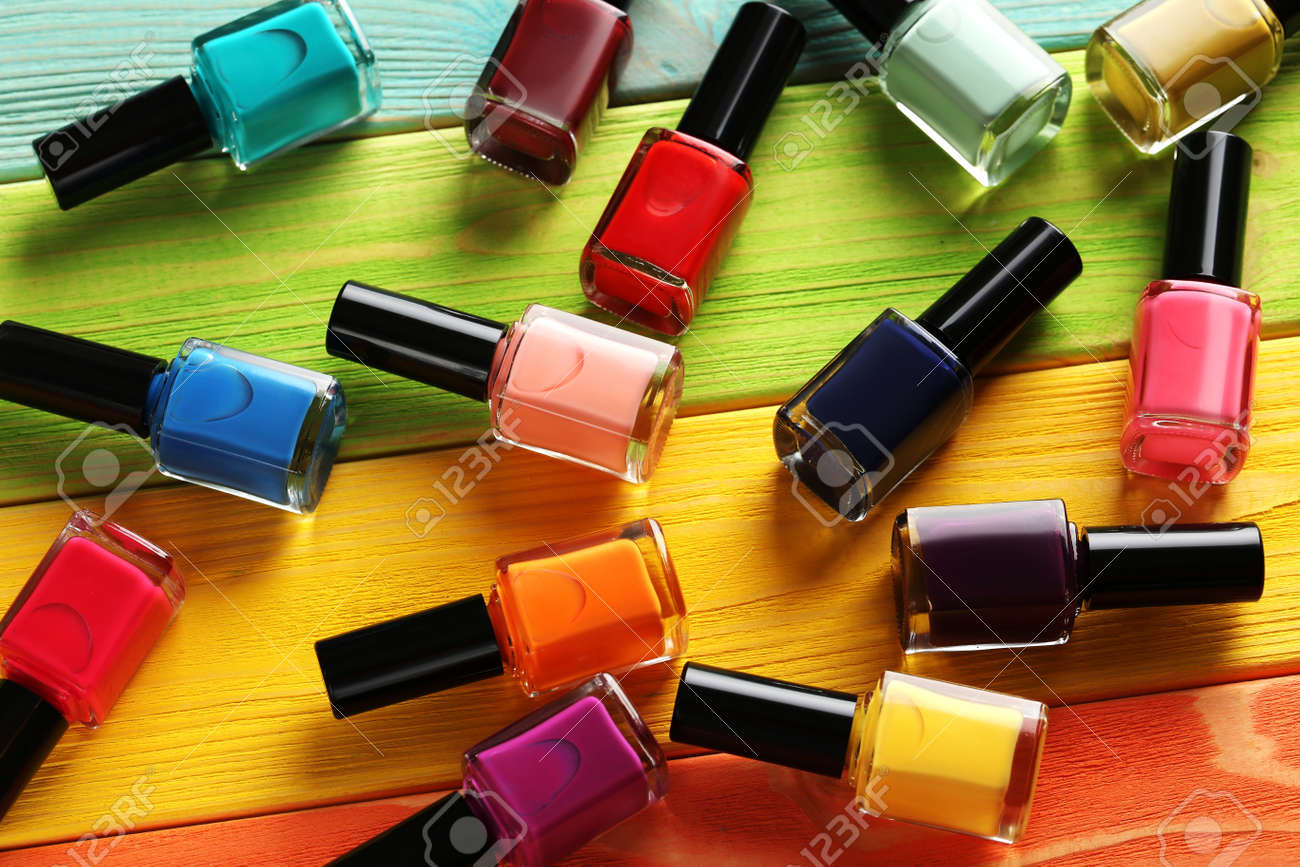 Bottles of nail polish on a colorful wooden table - 52450778