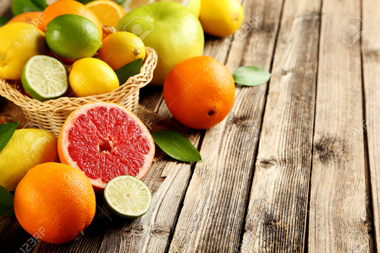 Citrus fruits on a brown wooden table - 52852529