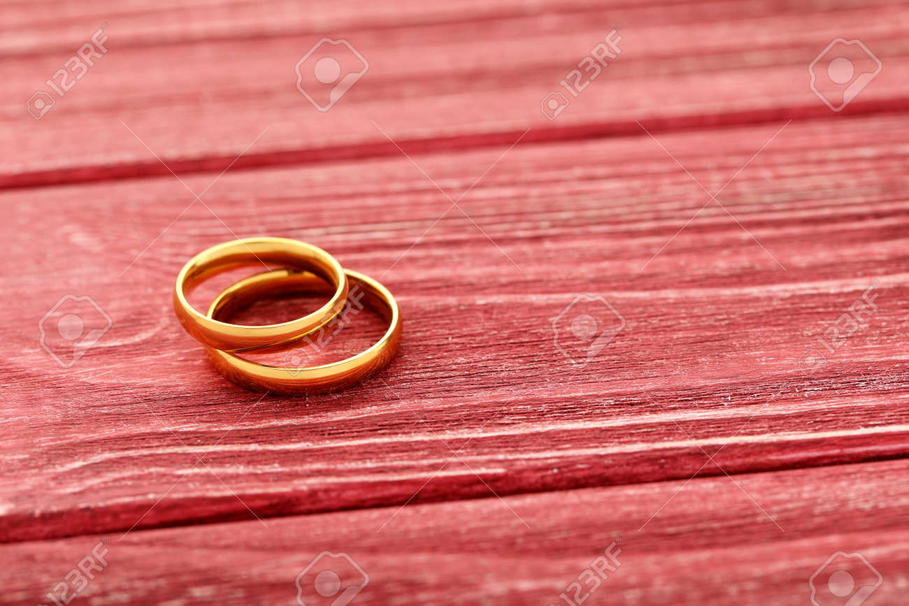 Golden Wedding Rings On A Red Wooden Table Royalty Free Stok ...