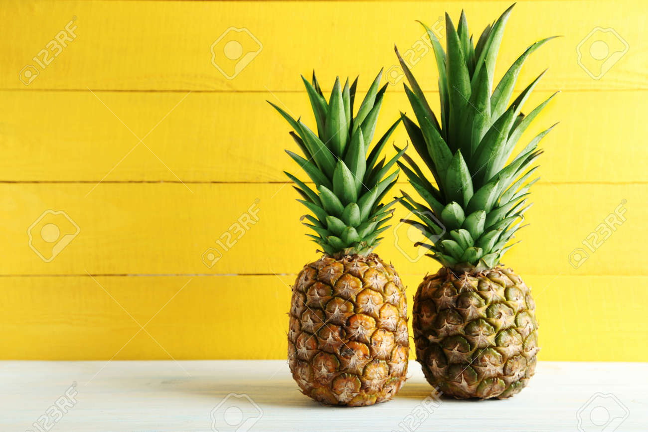 Ripe pineapples on a white wooden table - 53496712