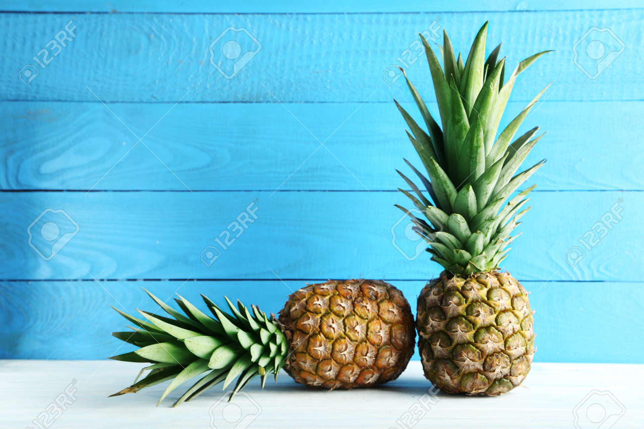 Ripe pineapples on a white wooden table - 55008567