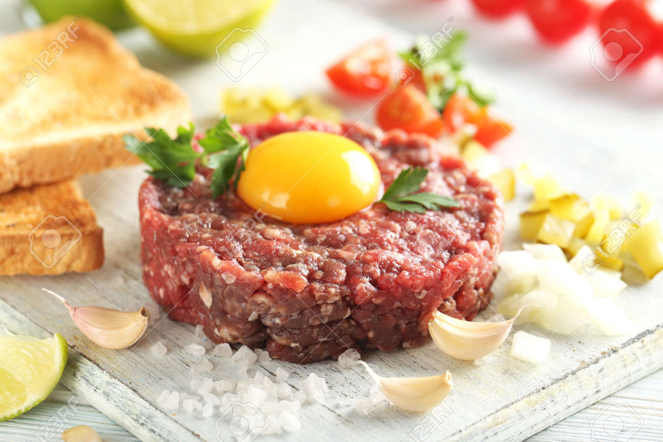 Beef tartare with egg yolk on a blue wooden table - 56732955