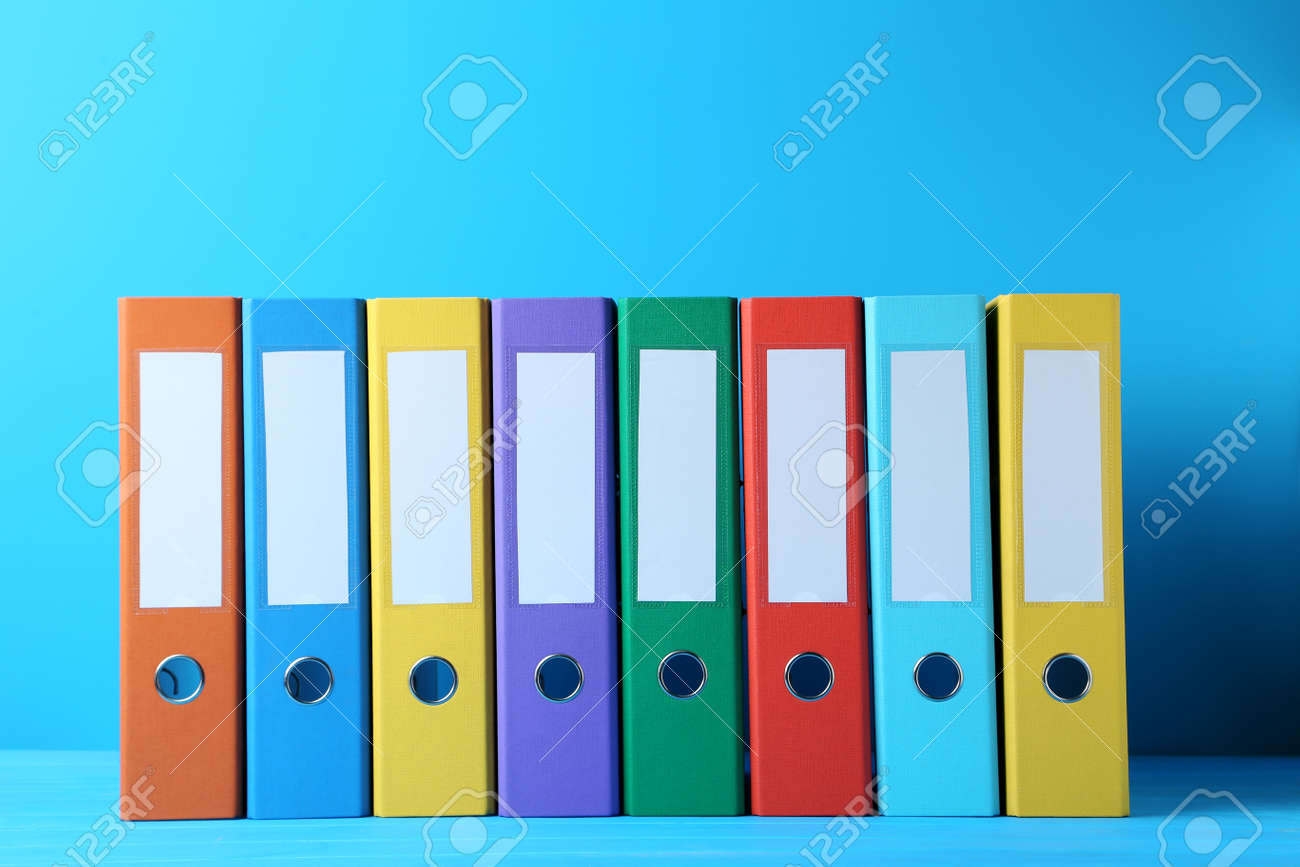 Colorful office folders on blue background - 80986196