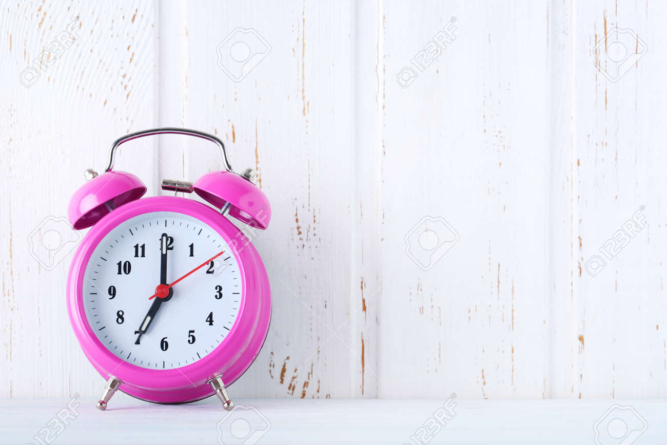 Pink alarm clock on white wall paneling background