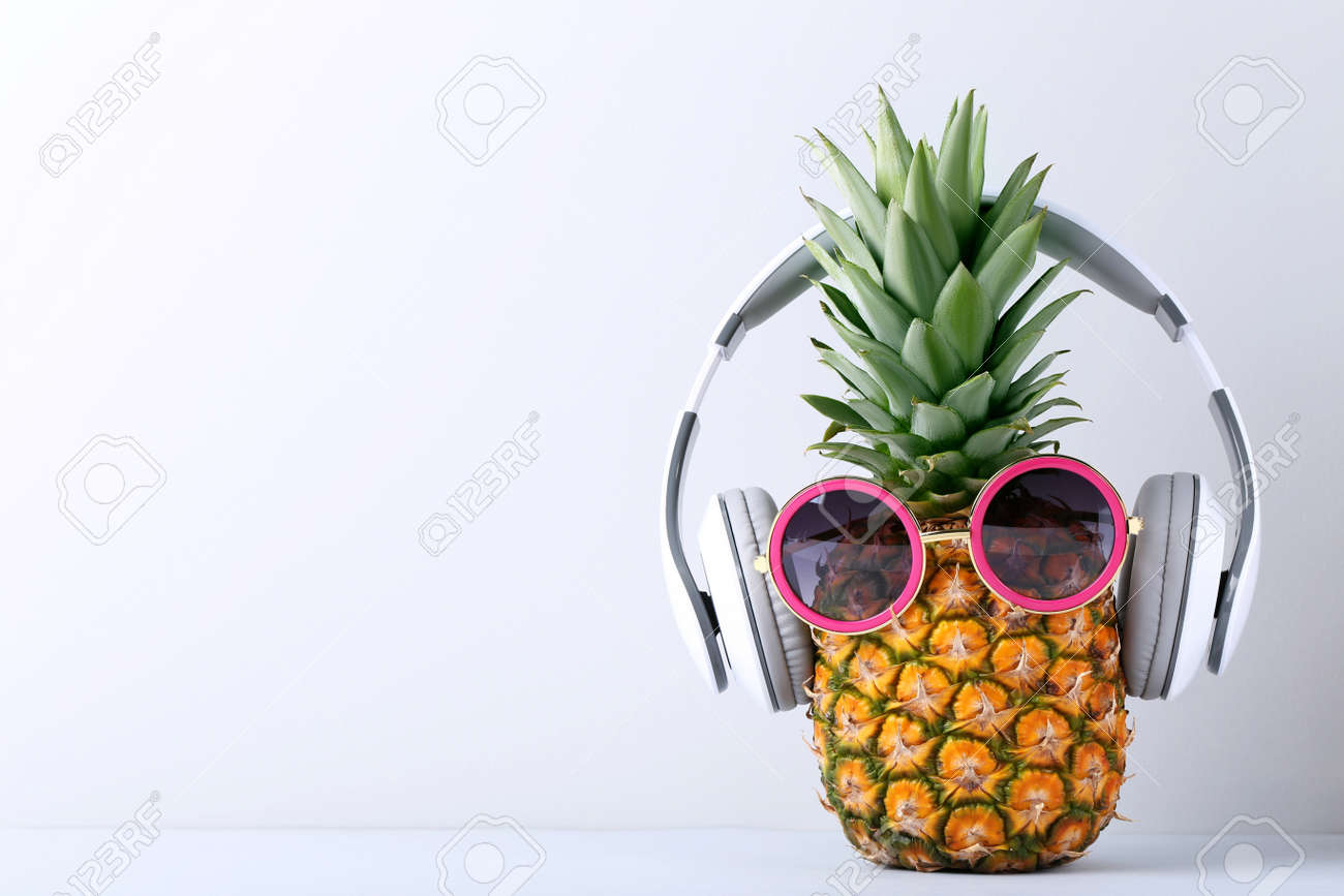 Ripe pineapple with headphones on grey background - 80205577
