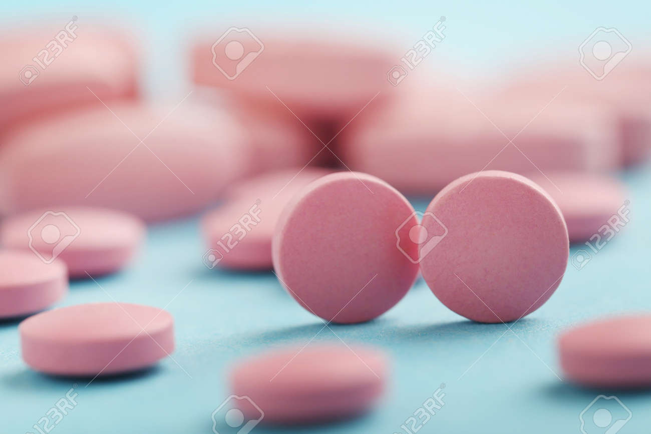 Heap of pink pills on blue background - 81067276