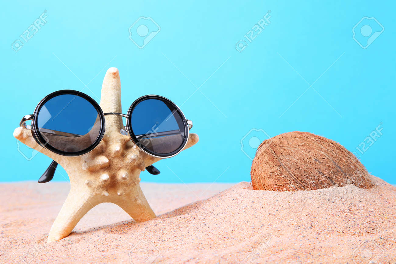 7adedfa419c Coconut with starfish in sunglasses on the beach sand Stock Photo - 86298312