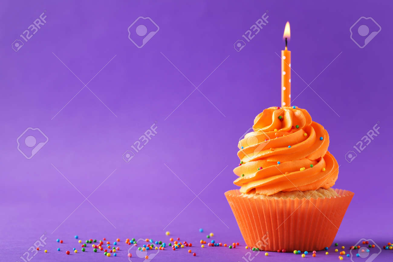 Tasty cupcakes with candle on a purple background - 87206672