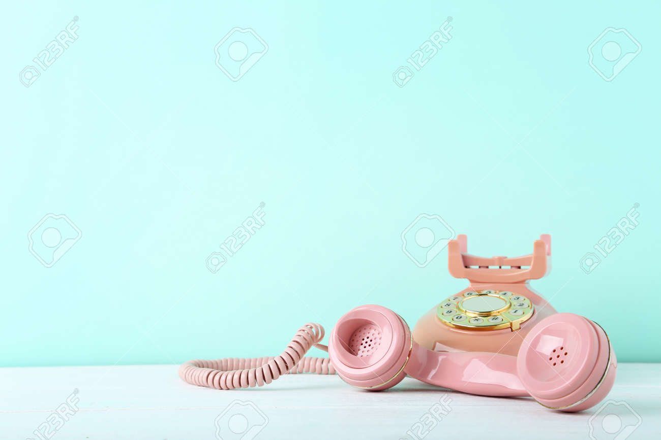 Pink retro telephone on white wooden table - 87516083
