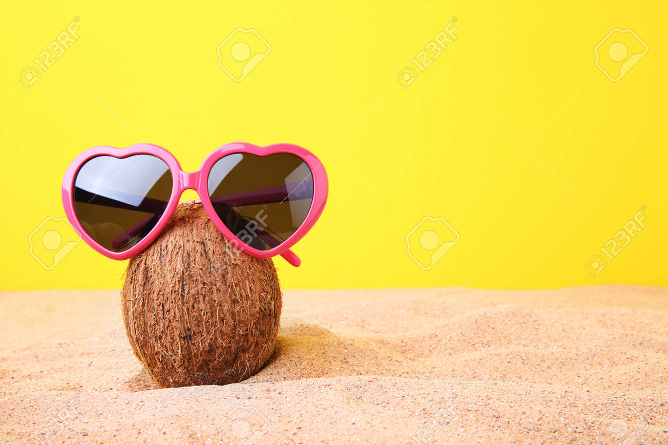 07d0d166e68 Coconut with sunglasses on the beach sand Stock Photo - 88551246
