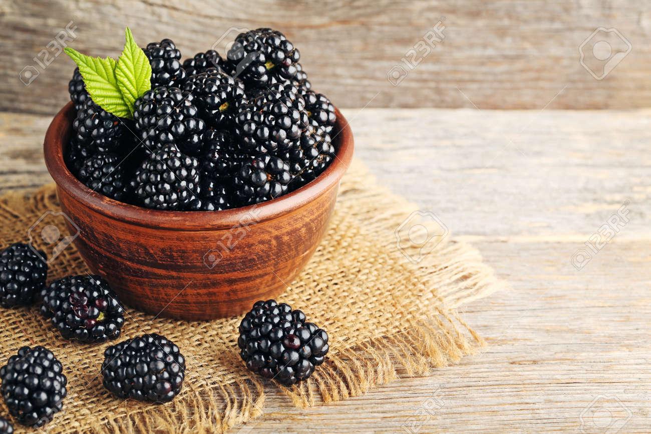 Ripe blackberries in bowl on wooden table - 88936157