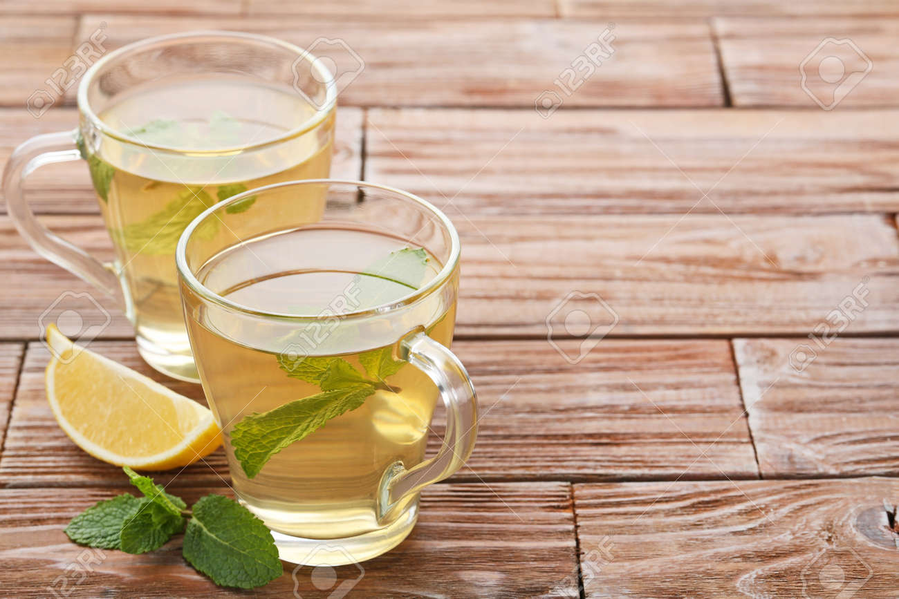 Cup of tea with mint leafs and lemon on wooden table - 90080194