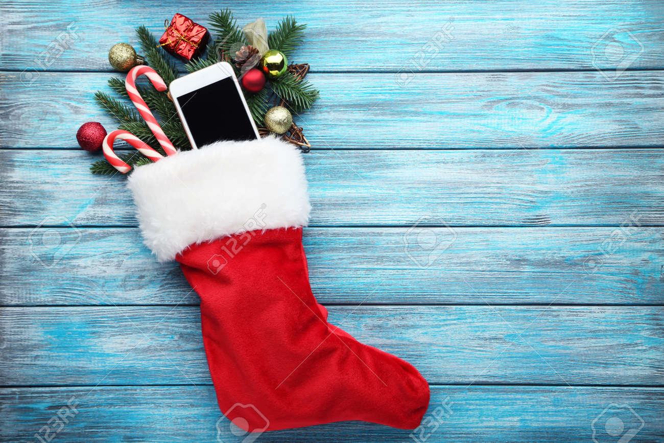 Red stocking with fir-tree branches and smartphone on wooden table - 90614371