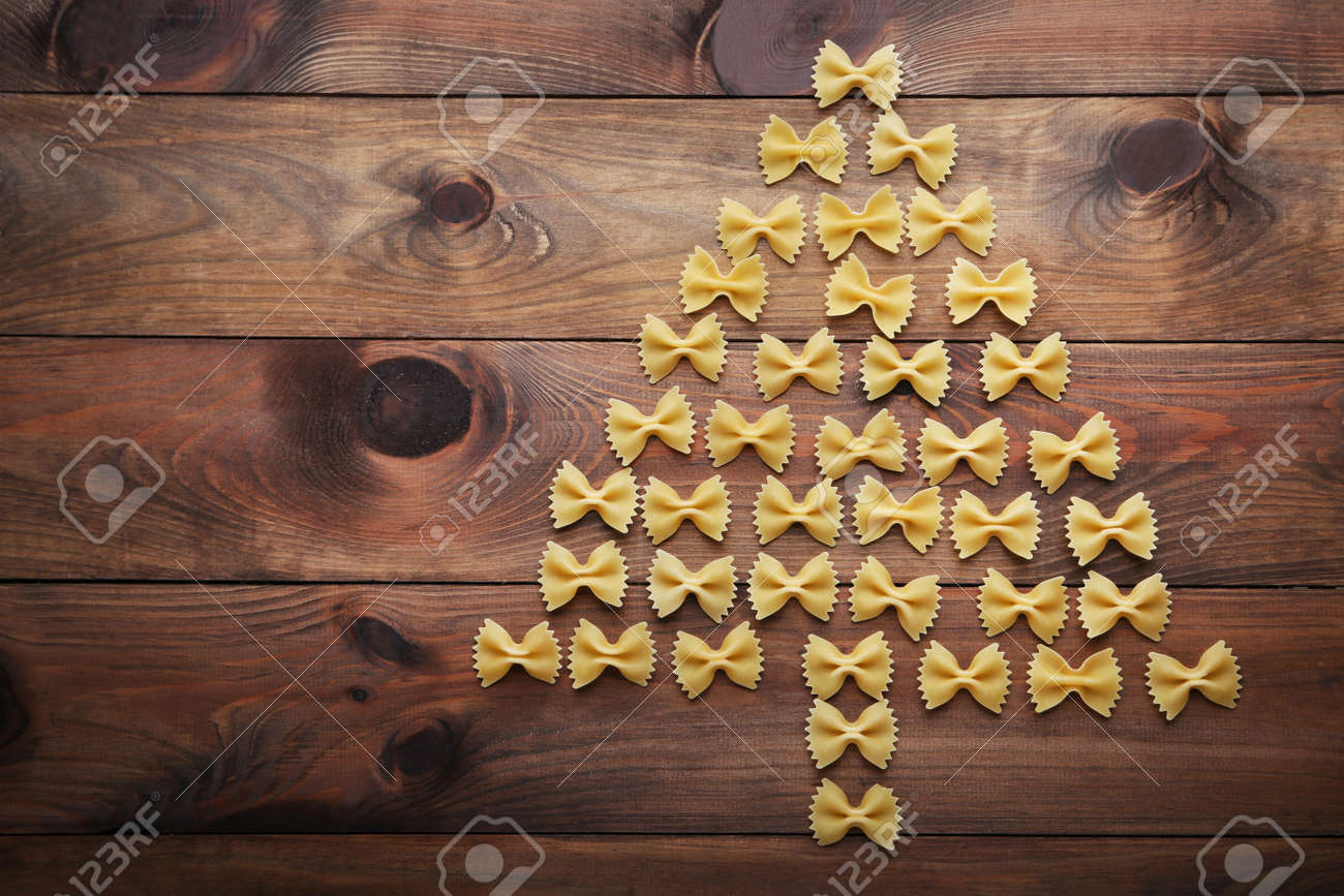 Christmas tree made from bow tie pasta on wooden table - 91253905