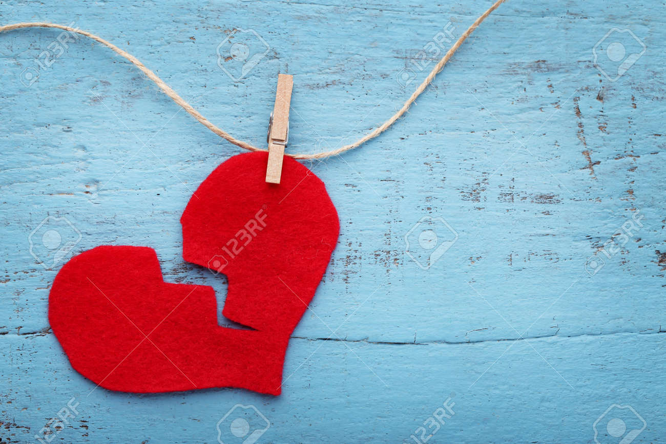 Broken red heart hanging on rope on blue wooden table - 92282614