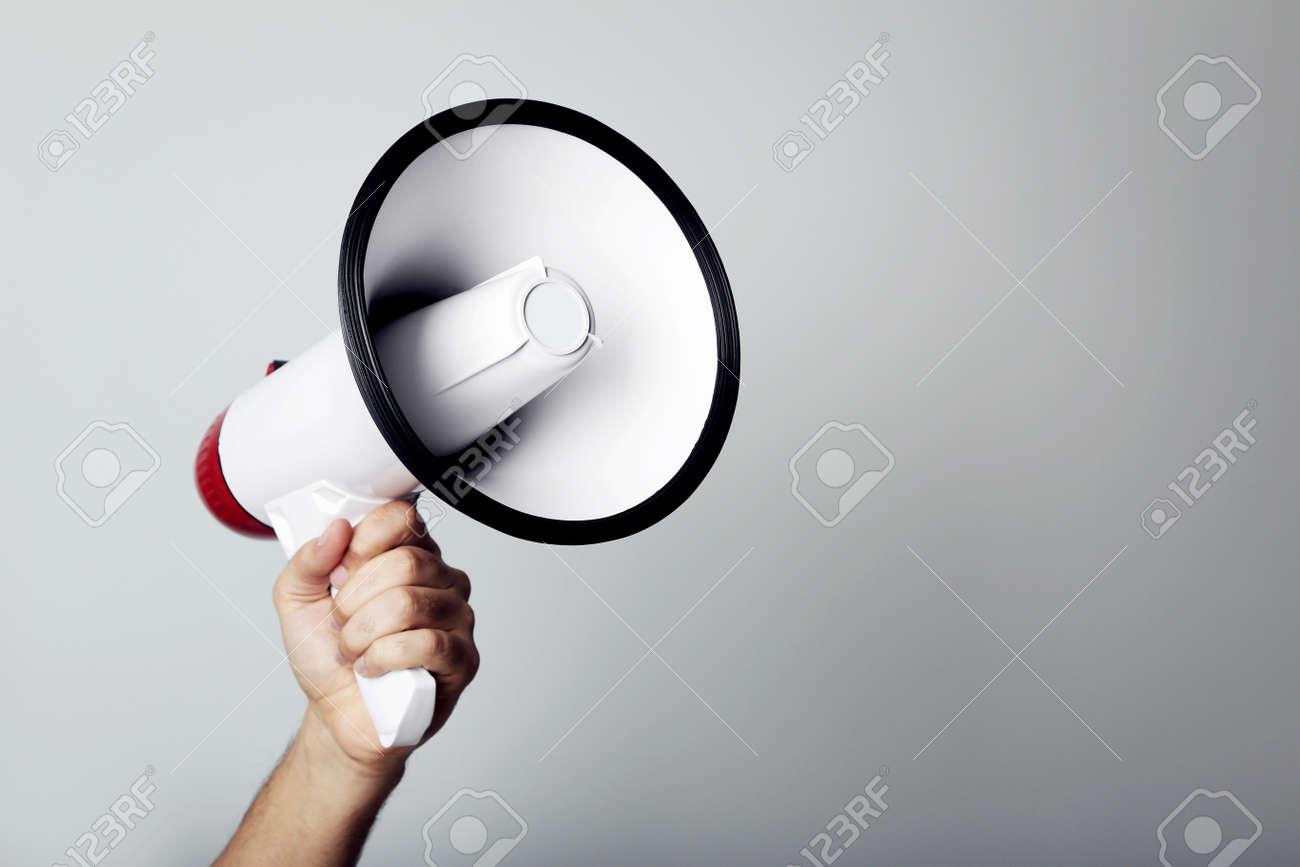 Female hand holding megaphone on grey background - 96380364