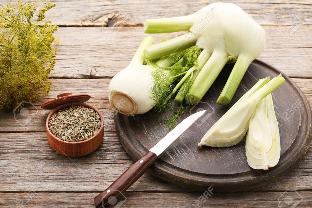 Ripe fennel bulbs and dry seeds in bowl on grey wooden table - 96380946