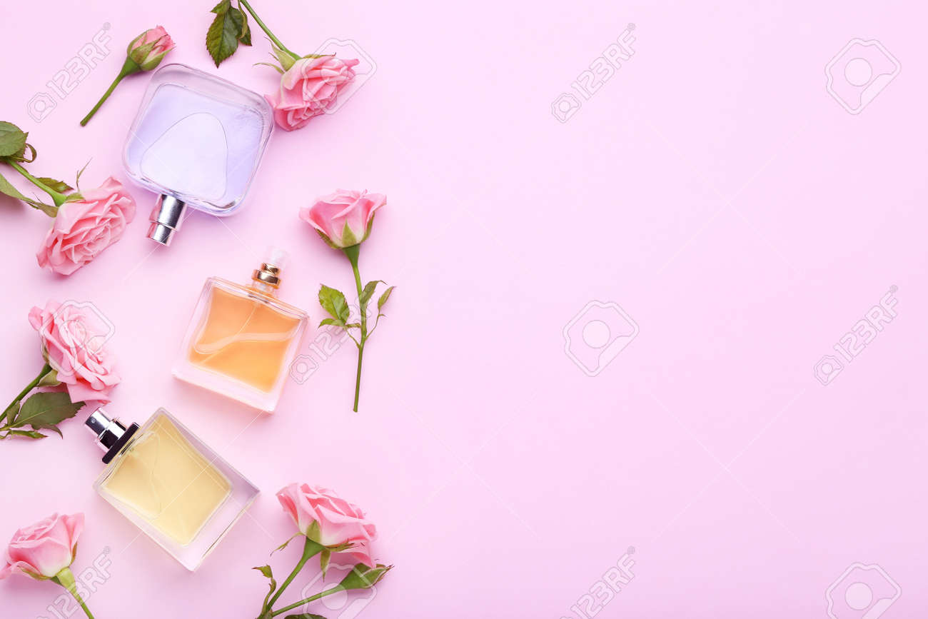 Perfume bottles with flowers on pink background - 97392381