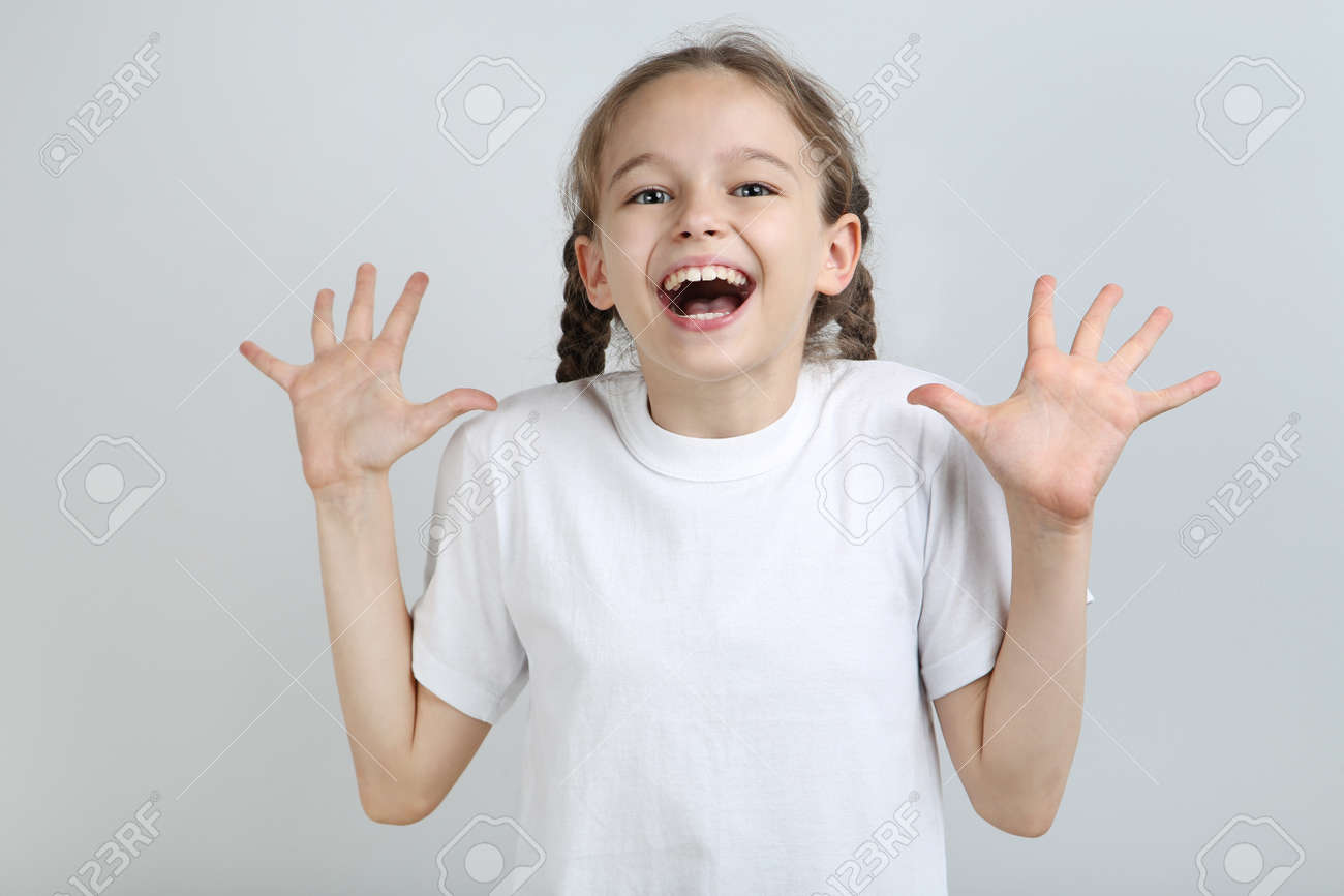 Surprised young girl on grey background - 104525777