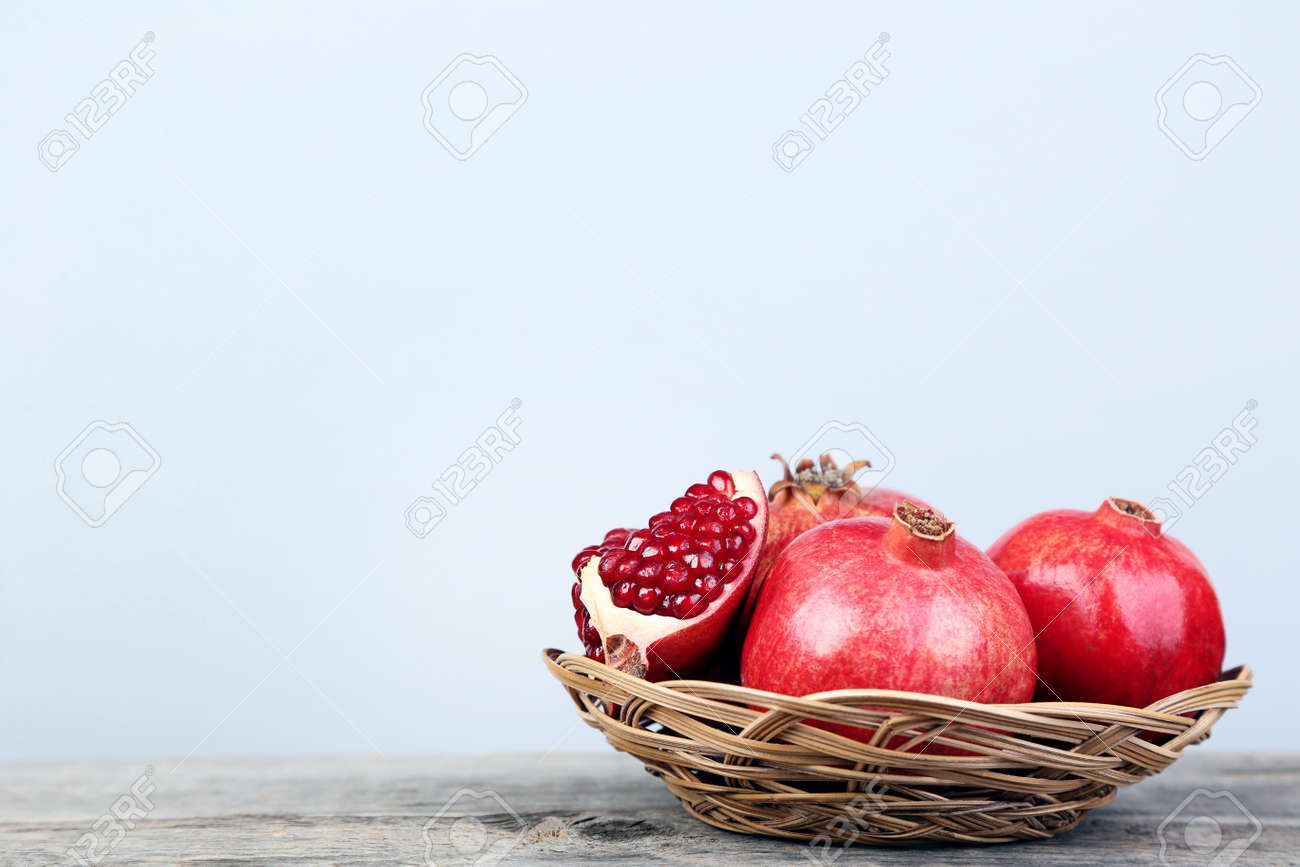 Ripe and juicy pomegranate in basket on grey wooden table - 104538306