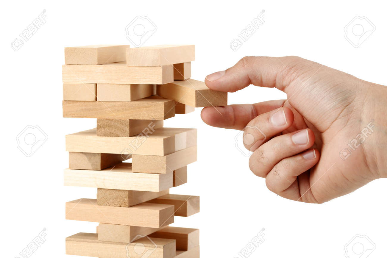 Male hand playing wooden blocks tower game on white background - 107070673