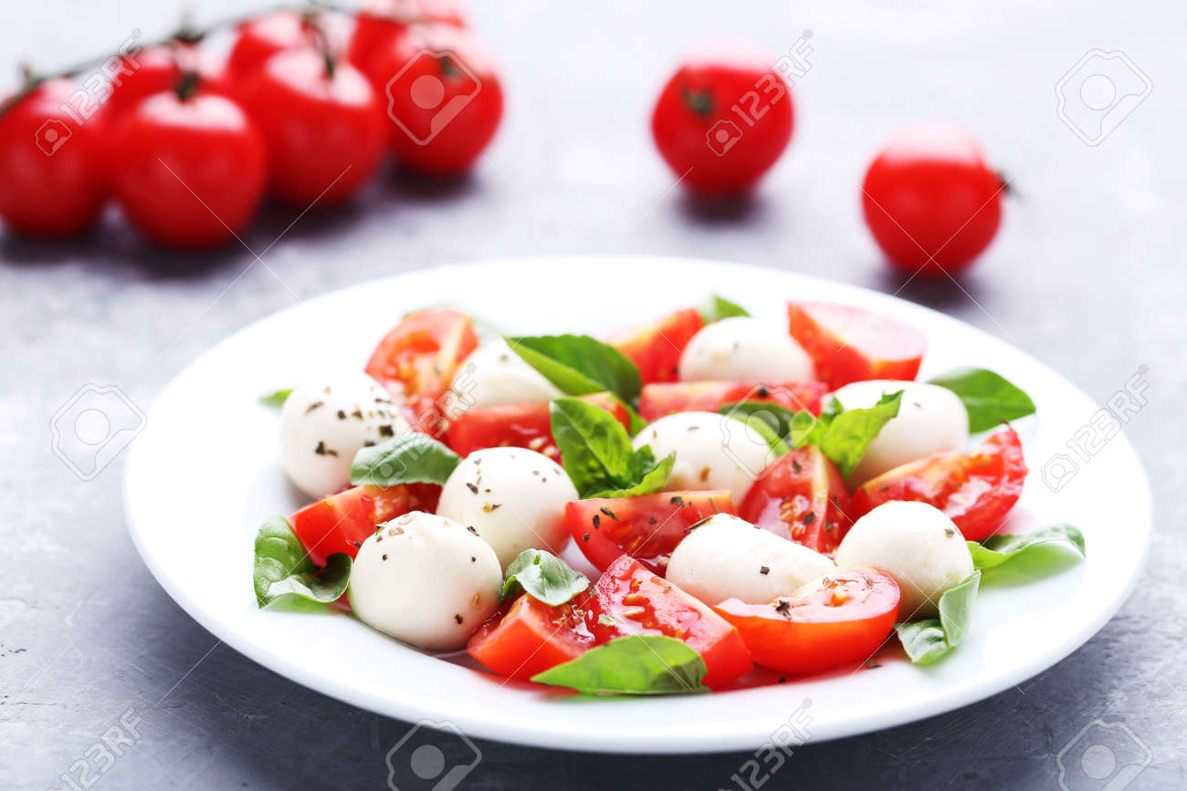 Mozzarella, tomatoes and basil leafs in plate on wooden table - 110047572
