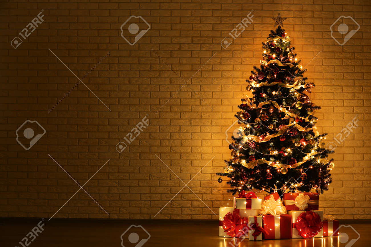 Christmas tree with decorations and gift boxes on brick wall background - 112577795
