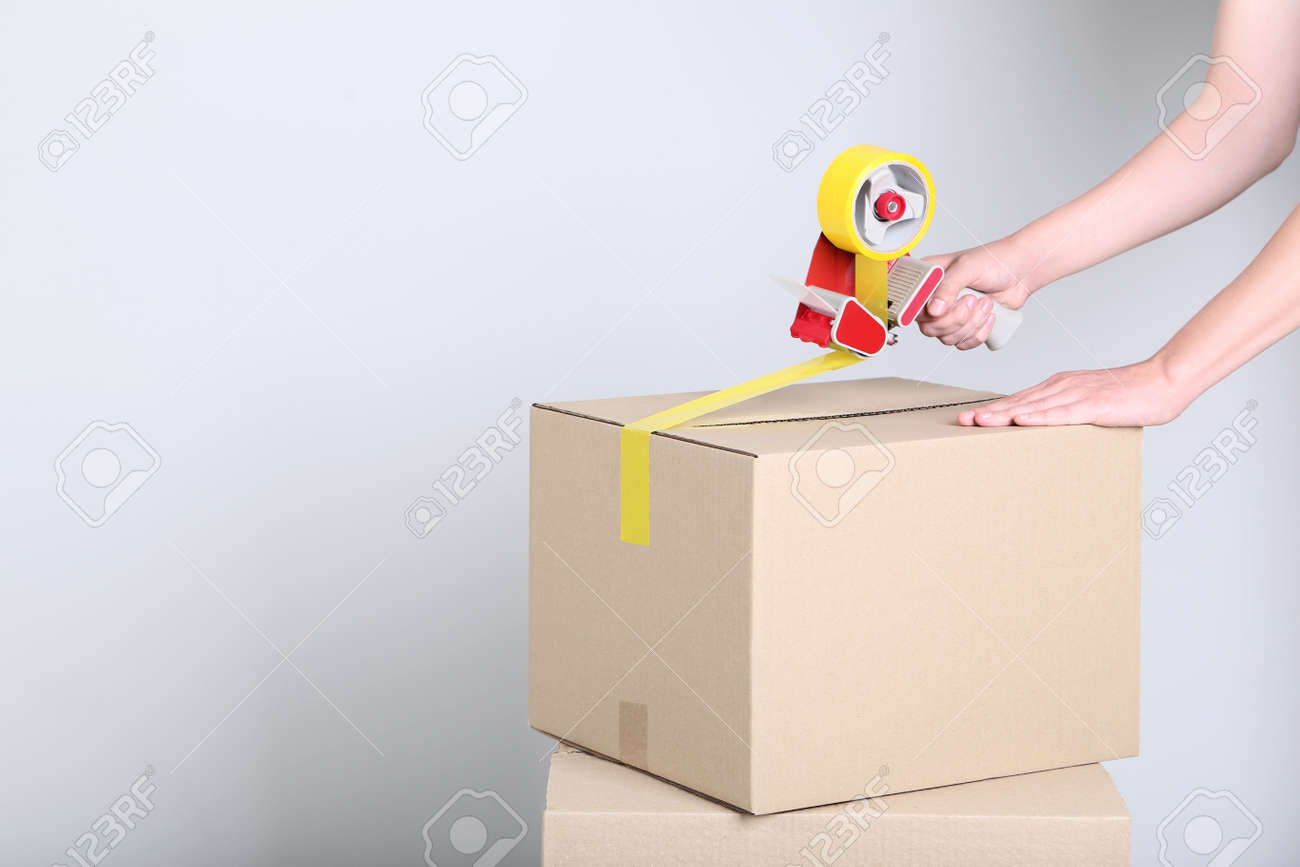 Female's hands packaging cardboard box with dispenser on grey background - 113295005
