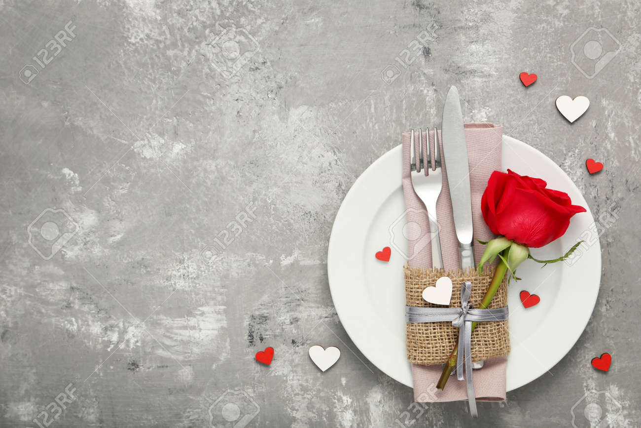 Kitchen cutlery with red rose in white plate on wooden table - 115383997