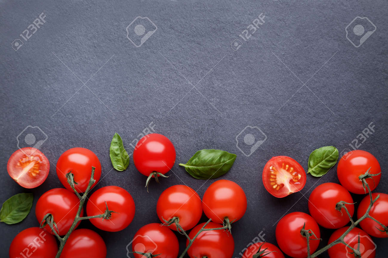 Cherry tomatoes with basil leafs on black background - 115989173