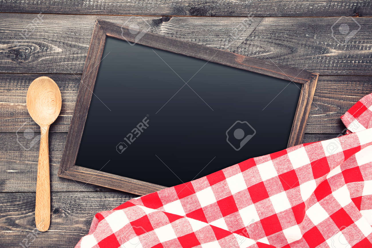 Blank chalkboard with red napkin and spoon on wooden background - 116434466