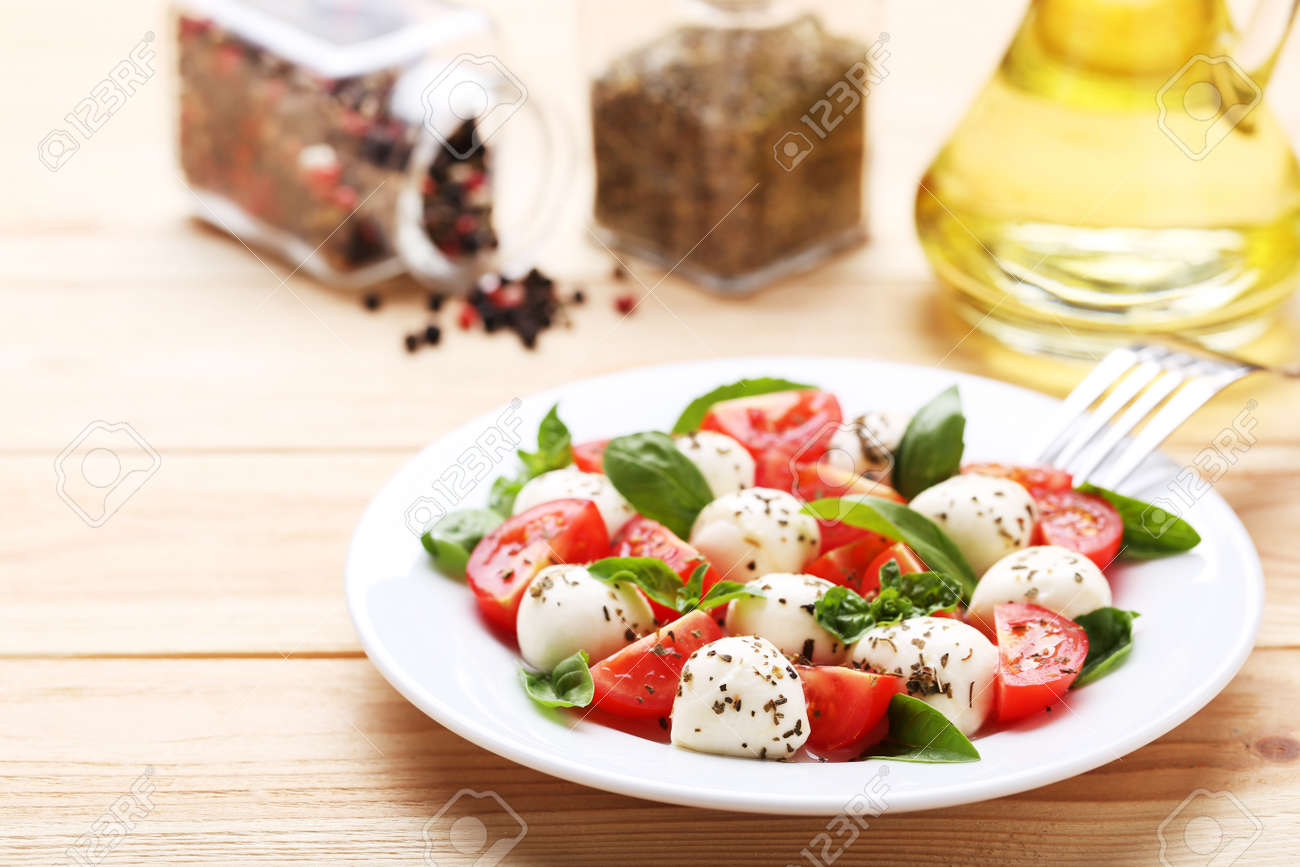 Mozzarella, tomatoes and basil leafs on brown wooden table - 116599513