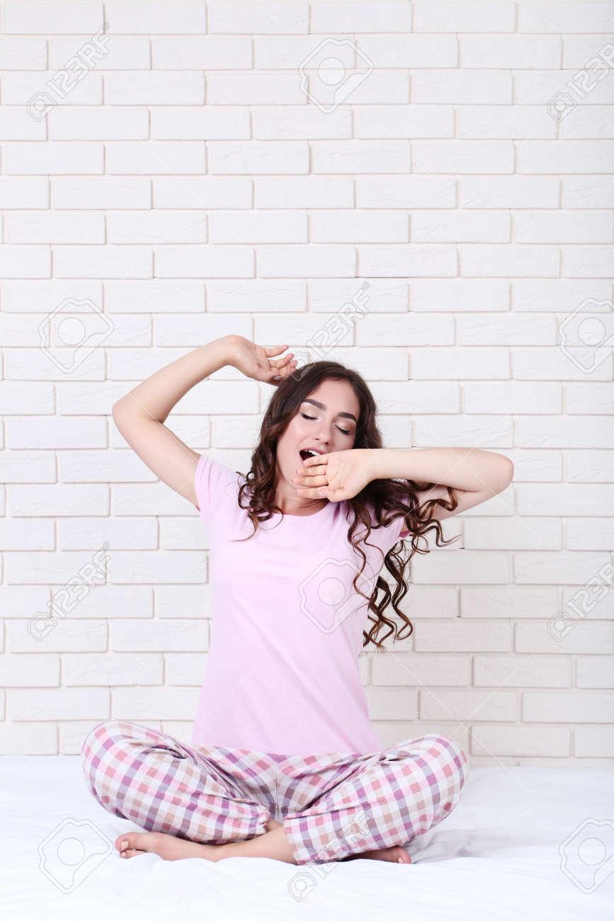 Yawning girl in pajamas sitting on white bed - 117748509